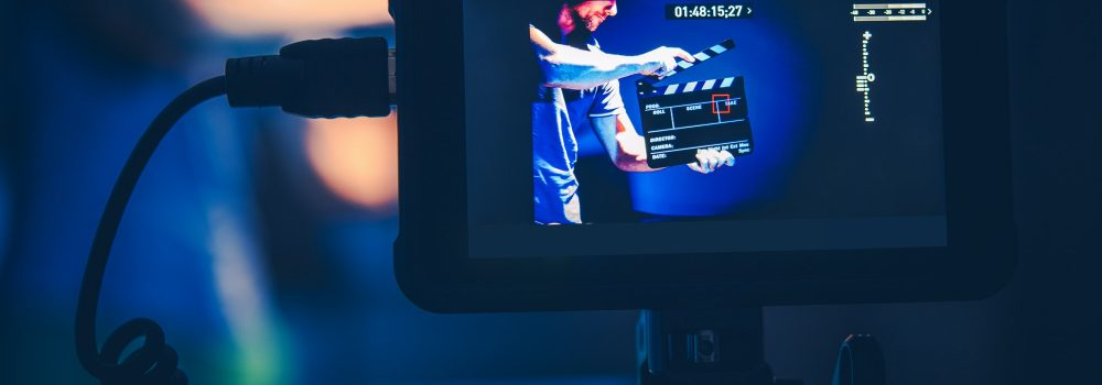 Camera Operator Taking Shots of Men with Clapperboard